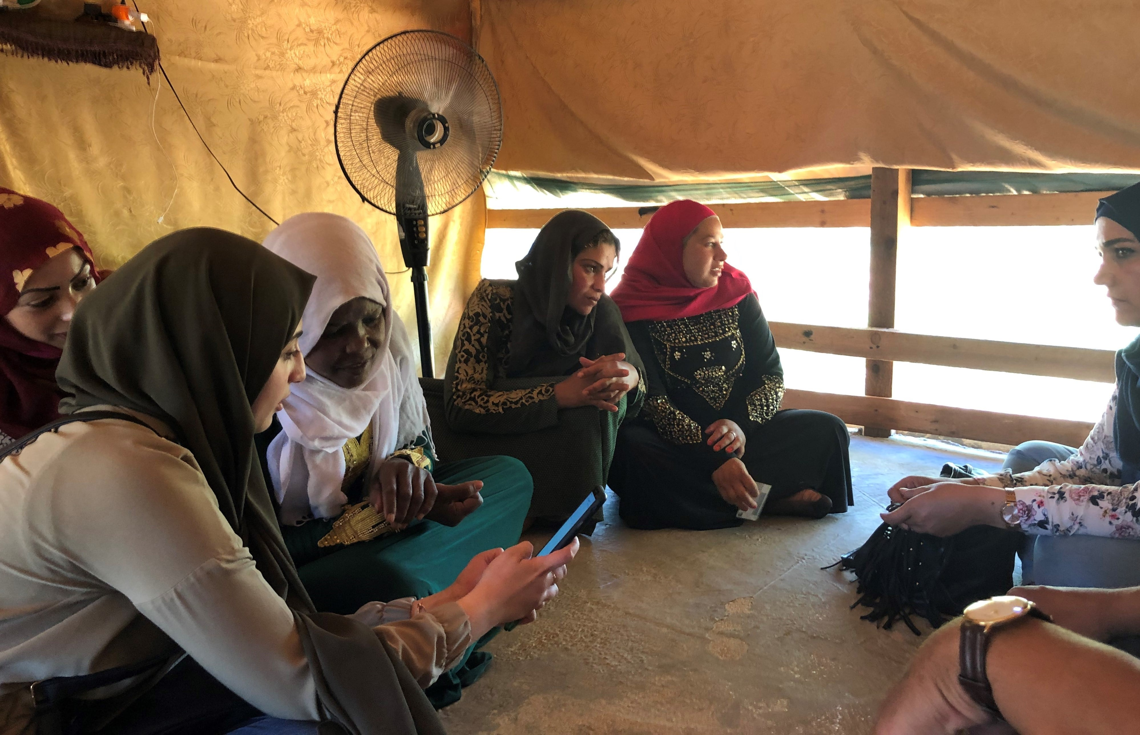 Photo description: Refugees receive a tutorial on Hawiyati, a digital identity solution developed by Making Cents International. Credit: Making Cents International,